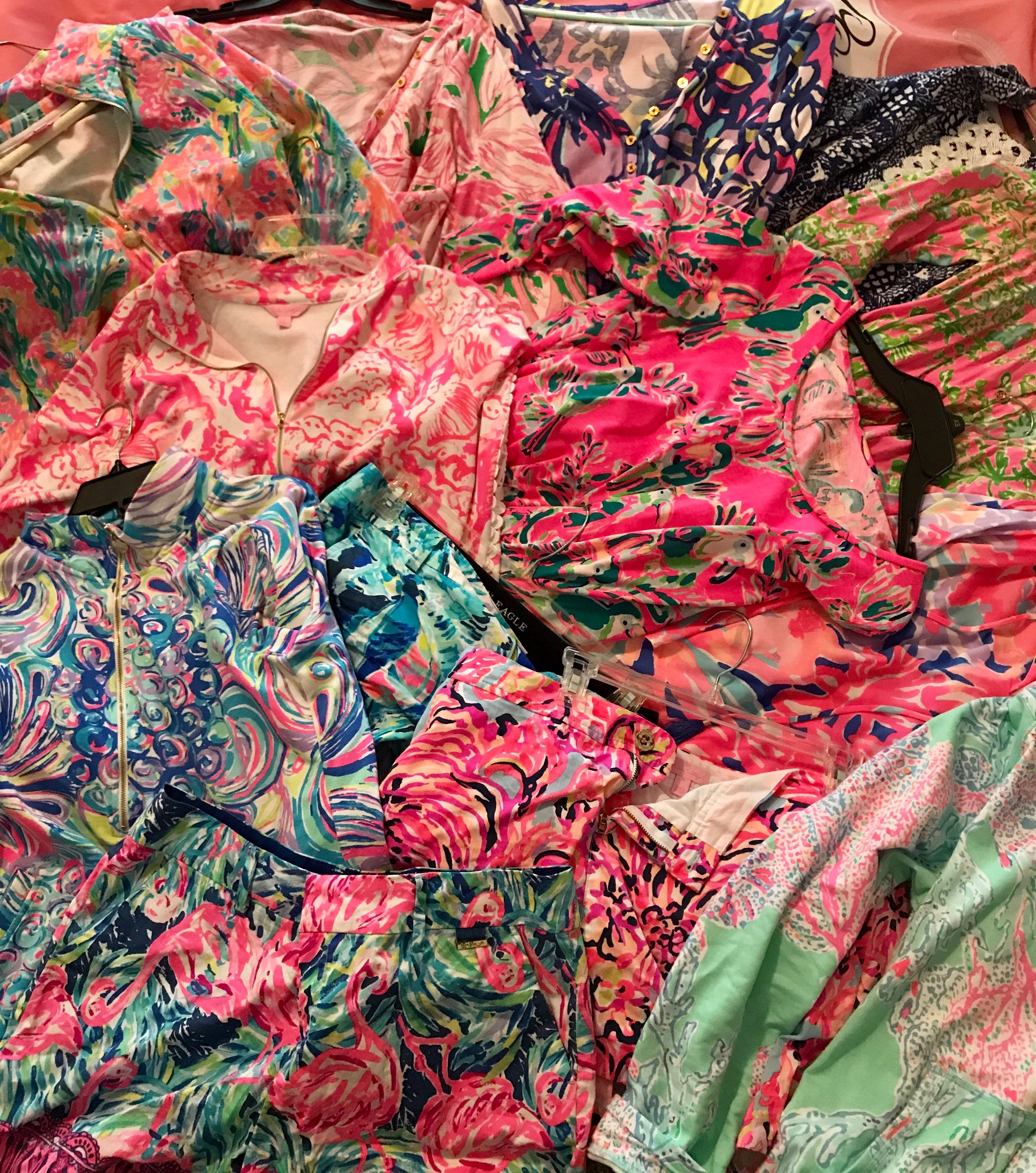 A pile of Lilly Pulitzer clothing from Tampa Blogger Ayana Lage, including a Gilty Pleasure popover, Coral Reef Beside the Point popover, flamenco beach callan shorts, minty fresh fantasy skipper popover, hey bae bae callahan shorts, fansea pants skipper popover, southern charm palmetto dress and more