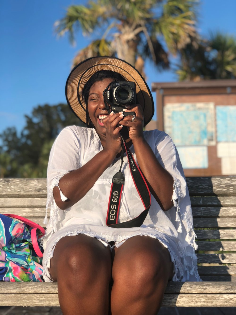 Tampa blogger Ayana Lage sits on a bench in Tarpon Springs, Florida. She is holding a Canon 60D camera while smiling at the camera. There is a Lilly Pulitzer Multi Casa Del Sol bag on the bench next to her.