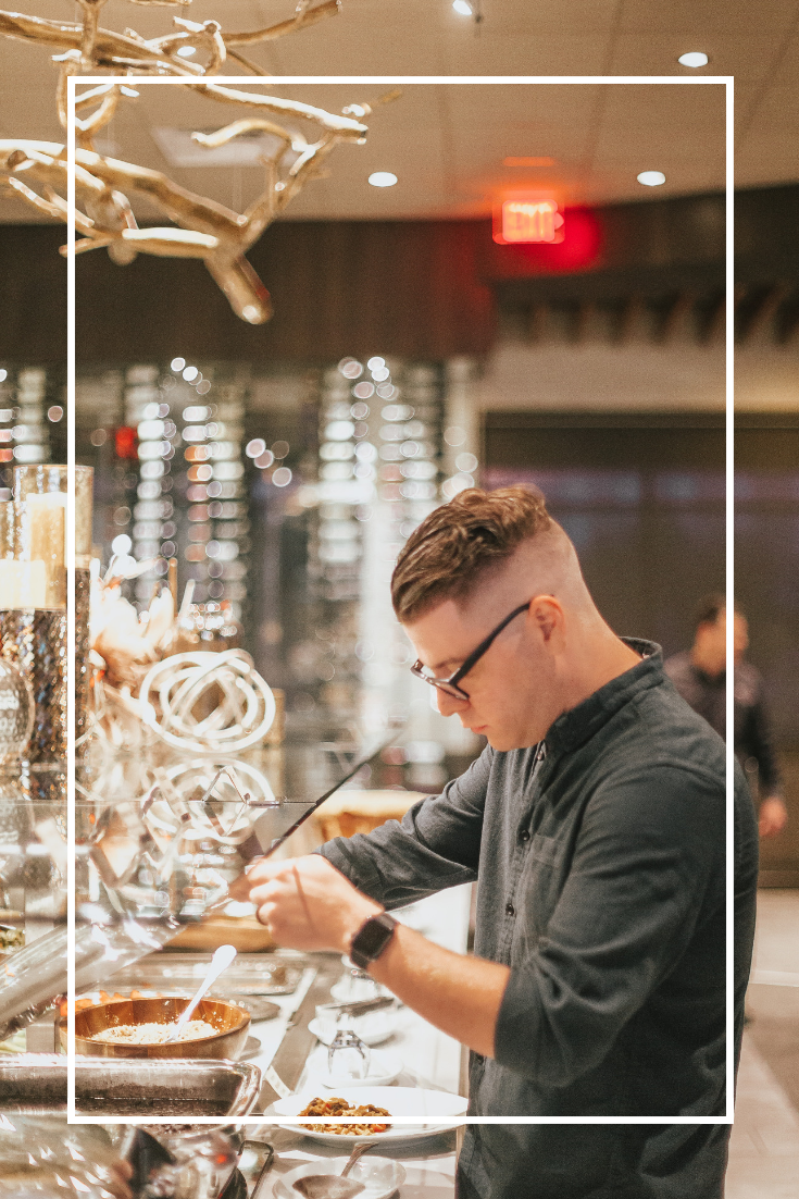 A man wearing glasses, an Apple watch and a green shirt stands in front of a salad bar at Terra Gaucha Brazilian Steakhouse in Tampa, Florida.