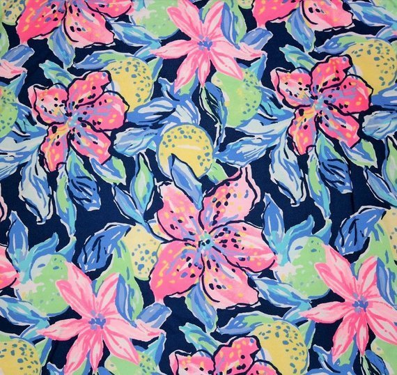 Lilly Pulitzer print with a fresh and beachy take on a floral pattern. Features vibrant yellow and green citrus fruits behind the coral and pink flowers, set on a classic navy background