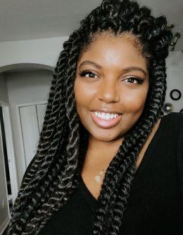 a woman smiles at the camera wearing a crochet hairstyle | A Guide To Crochet Hair