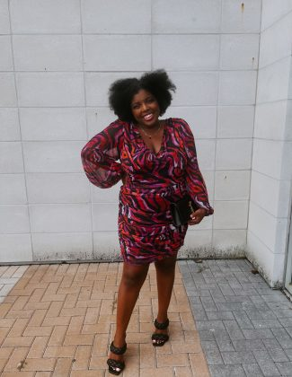 tampa blogger ayana lage stands in an ASOS dress outside of eddie v's in tampa, fl